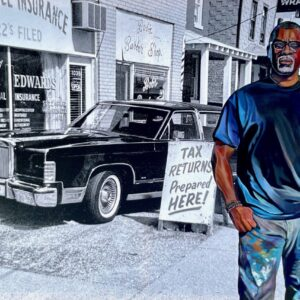 Painting of the artist on exhibit beginning July 9. He is picture in blue jeans and a blue t-shirt. He is a middle aged black male with his thumbs in his pocket looking directly at the viewer. In the background is a black and white painting of an old car.